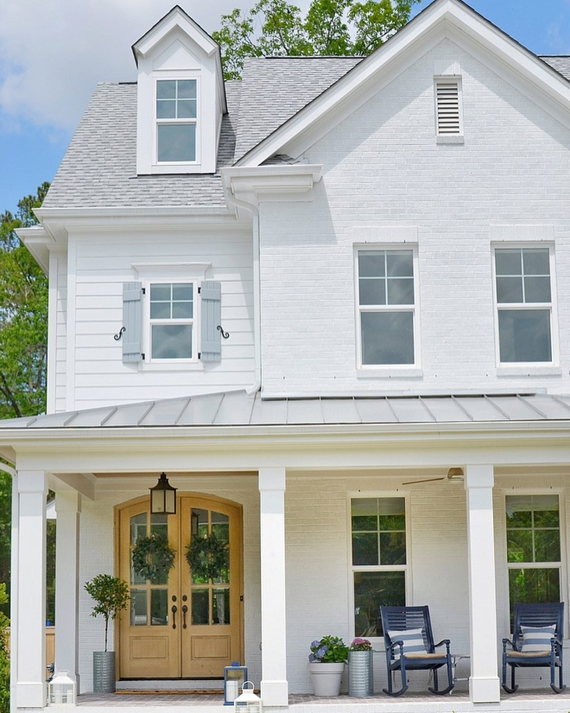 White farmhouse with gorgeous arched double doors and metal roof. Charming inspiration if you love white painted house exteriors! #whitehouses #housedesign #exteriors #whitefarmhouse
