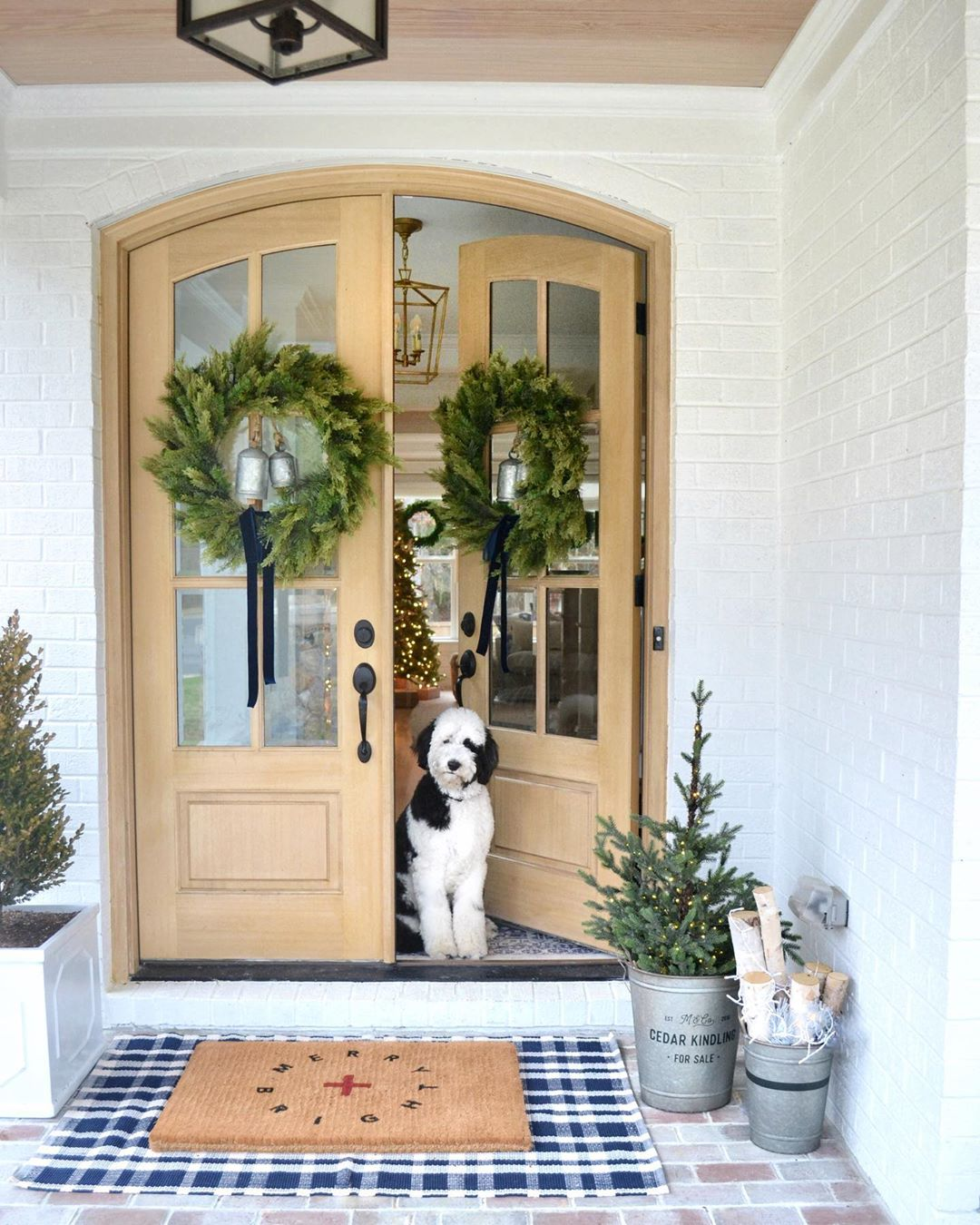 Holiday wreaths on front doors of white farmhouse with gorgeous metal roof. Charming inspiration if you love white painted house exteriors! #whitehouses #housedesign #exteriors #whitefarmhouse #holidaydecor #frontdoordecor #christmaswreaths