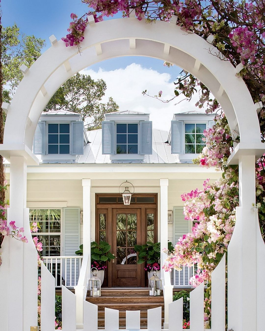 Breathtaking lovely curb appeal with amaazing floral covered arbor and blue shutters - Pineapples Design Group. Charming inspiration if you love white painted house exteriors! #whitehouses #housedesign #exteriors #curbappeal #shutters #arbor