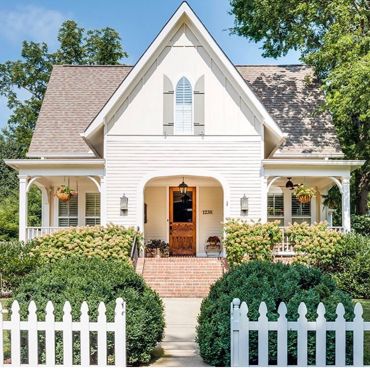 Welcoming cottage with arched entrance and front porch - Homes by Garden Gate. Charming inspiration if you love white painted house exteriors! #whitehouses #housedesign #exteriors #whitecottage #picketfence