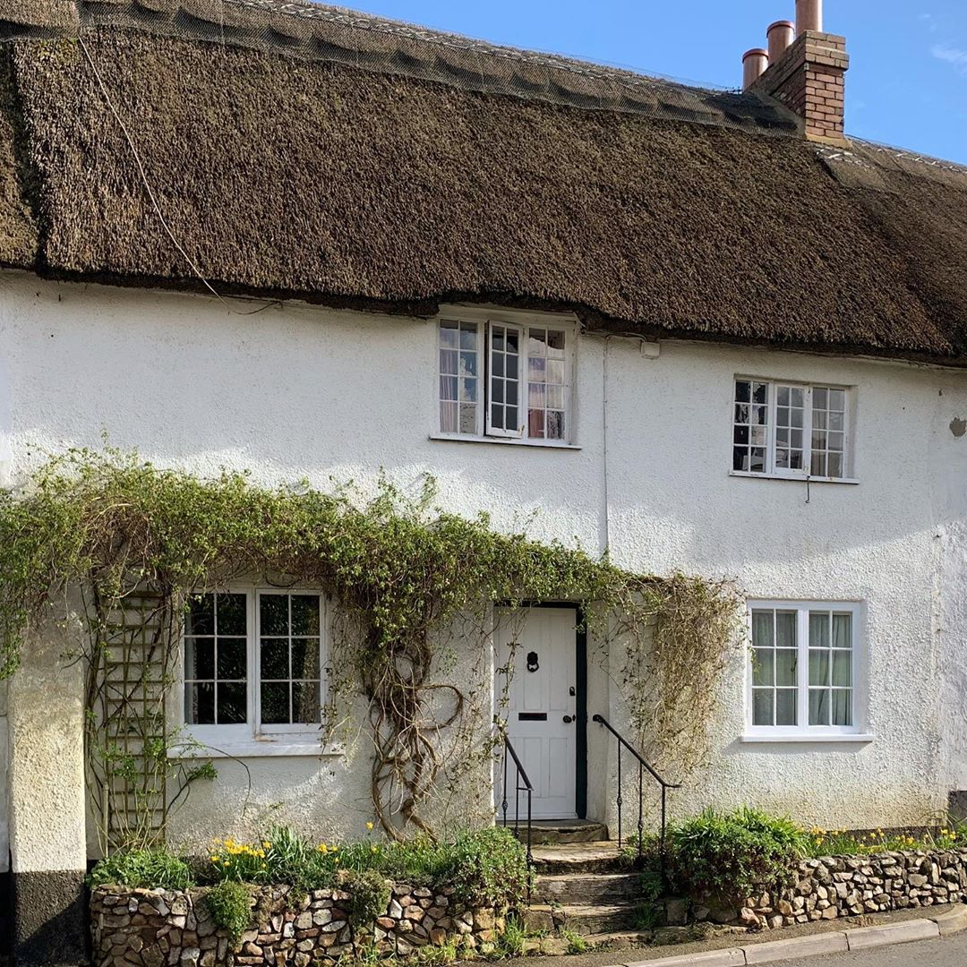 Charming white stucco English cottage home with thatched roof - Heart Felt Home.Charming inspiration if you love white painted house exteriors! #whitehouses #whitecottage #thatchedroof #englishcottage #whitestucco