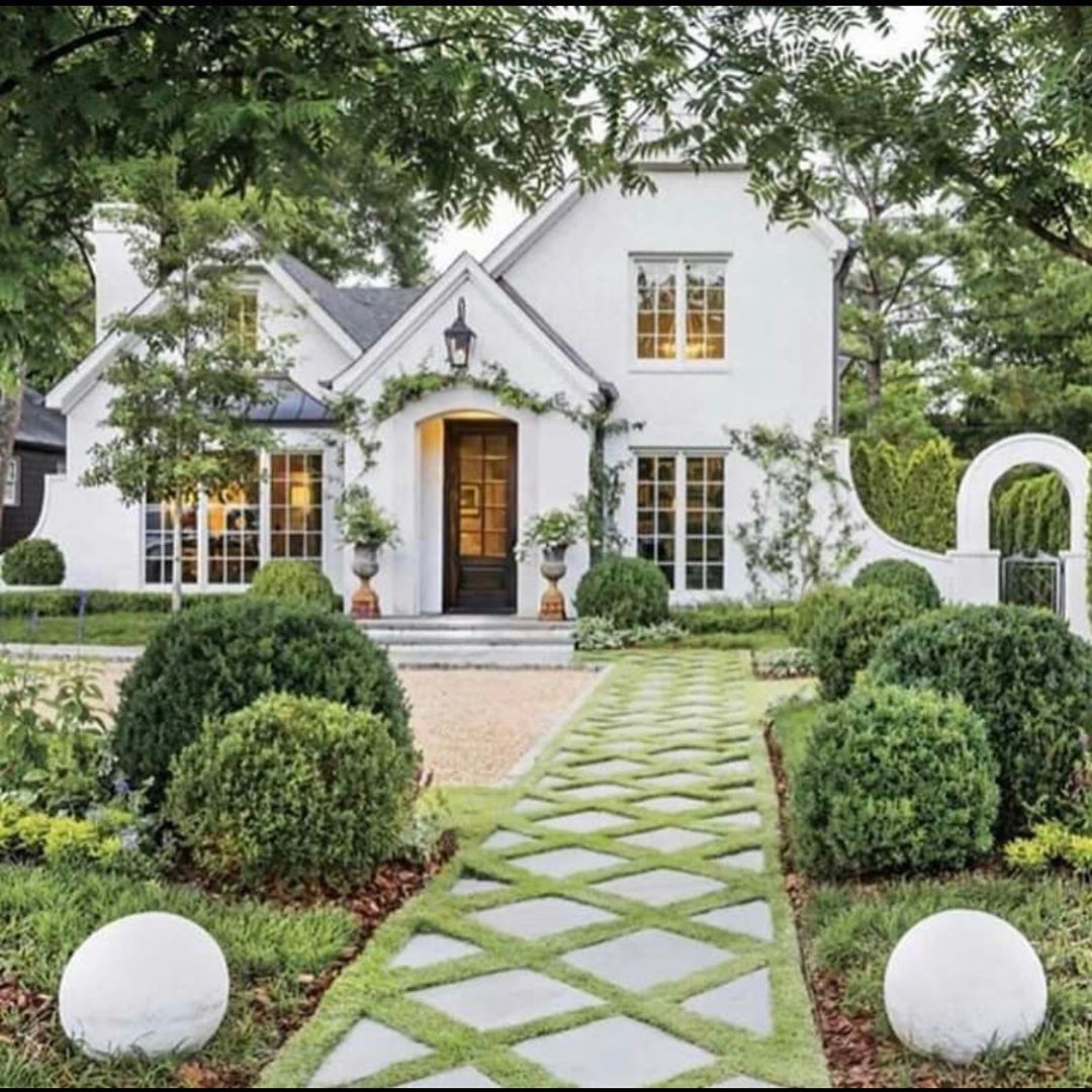 Exquisite lattice patterned landscaped walkway to charming white Tudor home - TMD Landscape Design. Charming inspiration if you love white painted house exteriors! #whitehouses #housedesign #exteriors #Tudor #landscapedesign #curbappeal