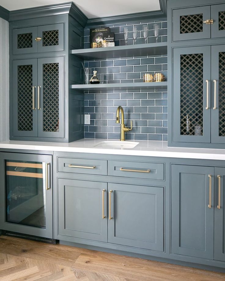 Gorgeous blue grey painted custom wet bar with subway tile and decorative inset grills in cabinet doors. Design: AGK Design Studio; Builder: @themeterco. #wetbar #bluegrey #customcabinetry #cabinetgrills