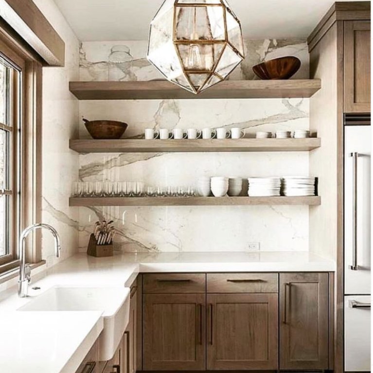 Gorgeous greyed wood cabinets and apron front farm sink in a gorgeous sophisticated neutral kitchen with elegant design. #farmsink #floatingshelves #kitchendesign