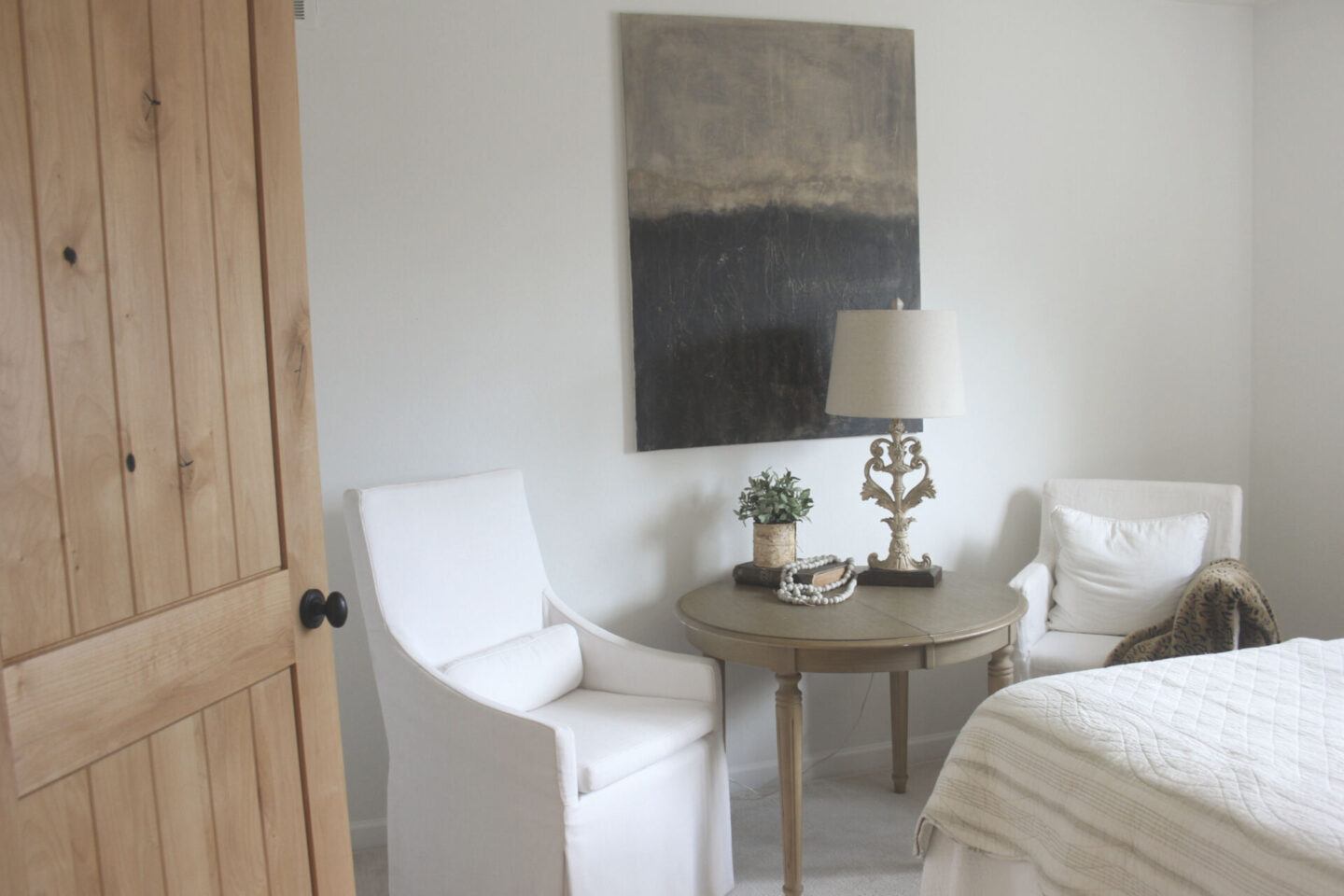Rustic knotty alder door opens into white bedroom with Belgian style furniture and abstract painting by Hello Lovely Studio. #alderdoor #europeancountrydecor #hellolovelystudio