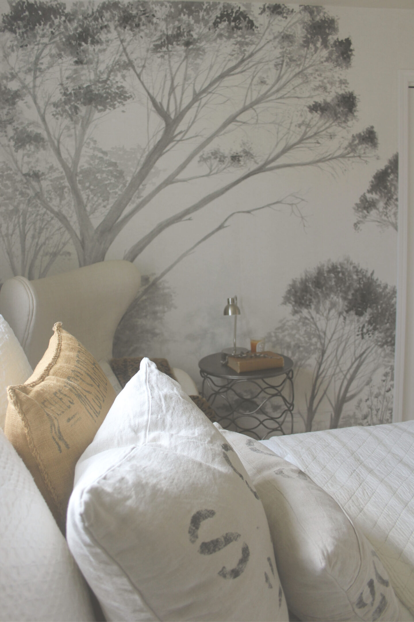 Lovely grisaille mural wallpaper from Photowall with grey trees on a white ground. I created a DIY accent wall in a guest bedroom, and the mood is timeless, serene and tranquil - Hello Lovely Studio. #wallpaper #mural #interiordesign #hellolovelystudio #grisaille #treewallpaper
