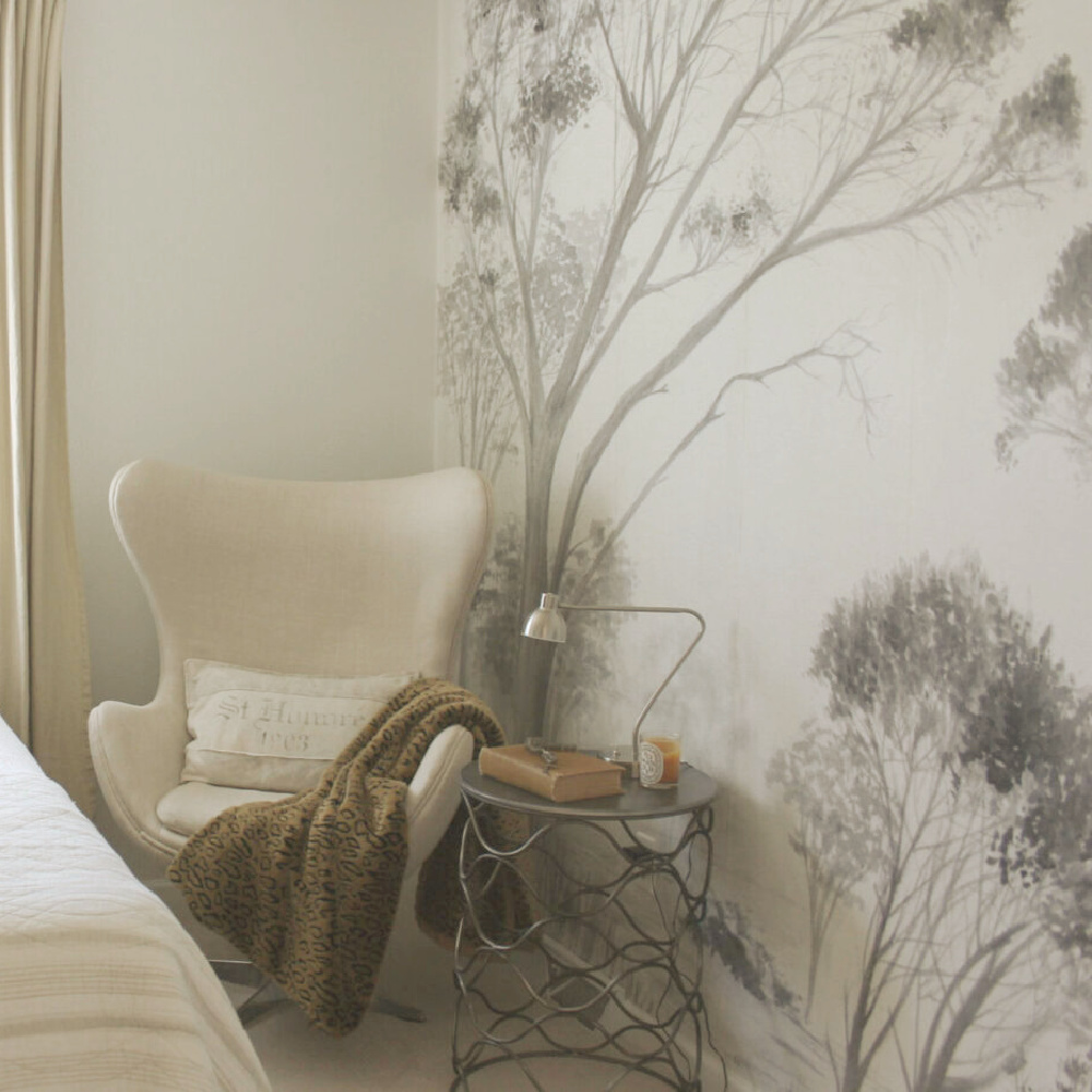 Beautiful grisaille mural wallpaper with trees in light grey on a white ground in a guest bedroom with neutral decor and egg chair - Hello Lovely Studio. #mural #muralwallpaper #grisaille
