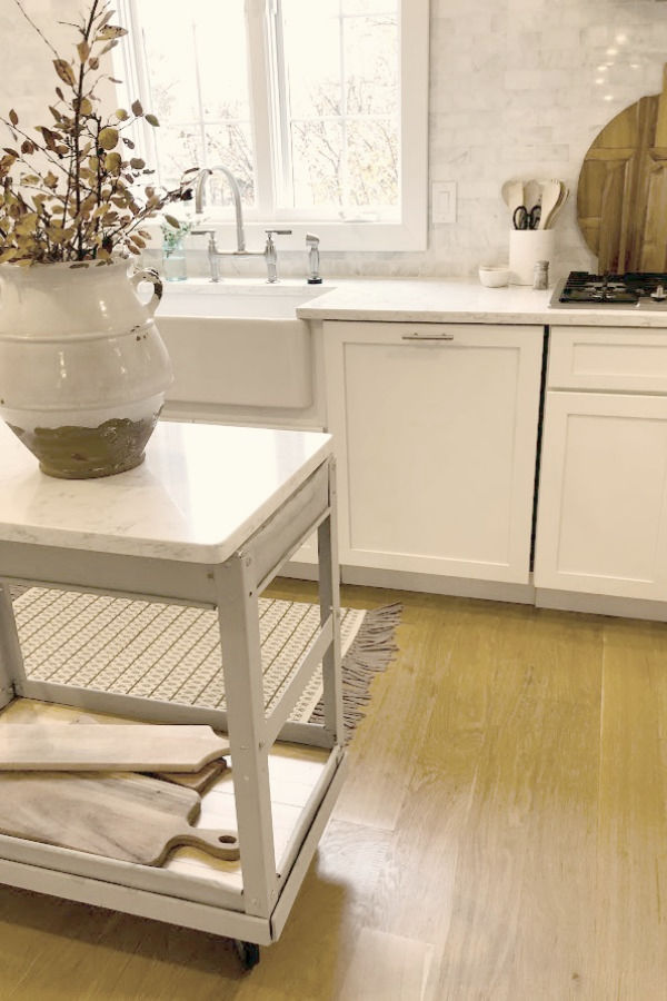 My simple white Shaker kitchen with white oak hardwood floor and vintage work cart - Hello Lovely Studio.