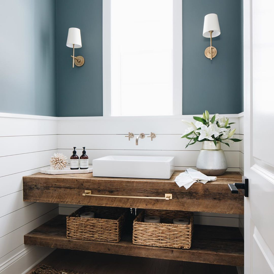 Modern farmhouse bathroom with gorgeous custom rustic wood vanity, rectangle fireclay farm vessel sink, wall mount faucet, shilap backsplash, and moody blue grey walls. Julie Howard for Timber Trains Homes (Western Springs, IL). Photo by Stoffer Photography Interiors #bathroomdesign #modernfarmhouse #bluegrey