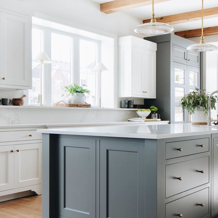 Gorgeous custom kitchen with blue grey island, white cabinets, beams, and Caesarstone counters including unique ledge and backsplash. Julie Howard for Timber Trails Homes (Western Springs, IL). Photo by Stoffer Photography. #kitchendesign #bluegrey #kitchenisland #ceilingbeams #darkgray