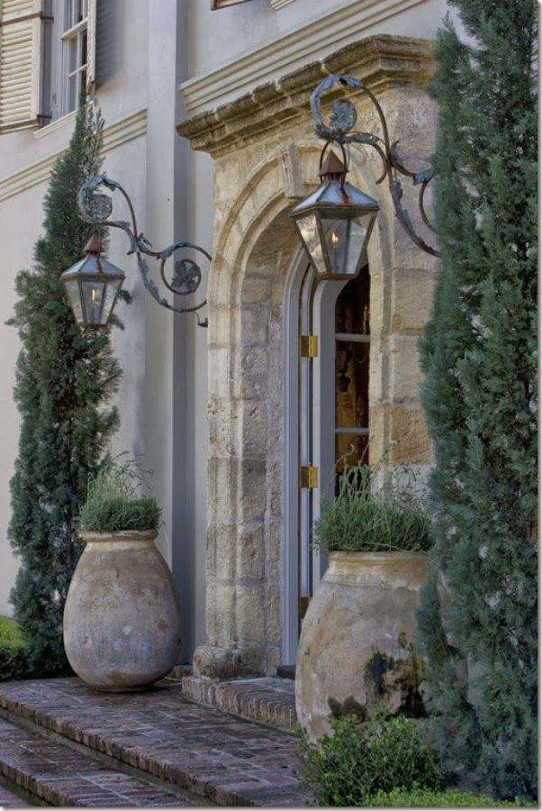 Pamela Pierce designed moment of French elegance with antique olive pots flanking an arched stone entrance with lanterns. #pamelapierce #frenchcountry #olivejars #stonesurround #frontdoor #archeddoor