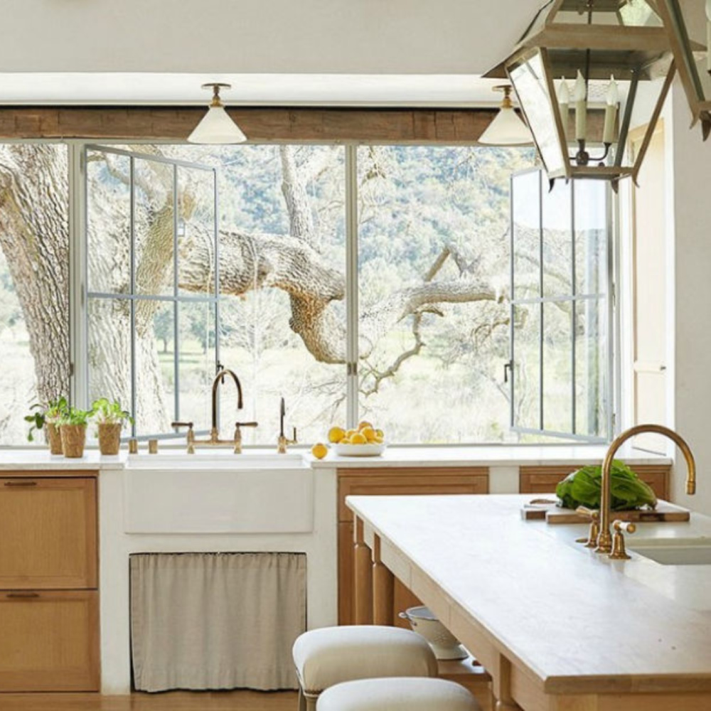 Patina Farm kitchen with white oak cabinets, farm sink, and steel windows - Giannetti Home and Brooke Giannetti. #patinafarm #frenchfarmhouse #farmhousekitchen #whiteoakcabinets #farmsink #lanternpendant #brookegiannetti