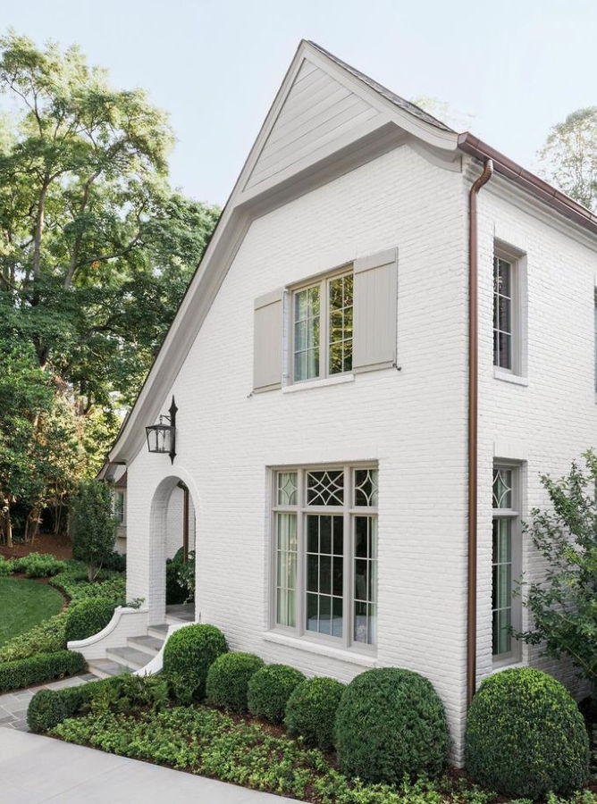 White brick home with arched entrance and light gray trim and shutters - Ladisic Fine Homes & Sherry Hart.. #benjaminmoore #balboamist #intellectualgray #houseexterior #paintcolors