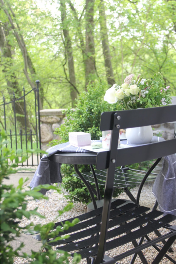 Lush green garden and a black French bistro set in my romantic courtyard. #hellolovelystudio #frenchcountry #bistrochairs #patiofurniture #romantidecor #outdoordecor