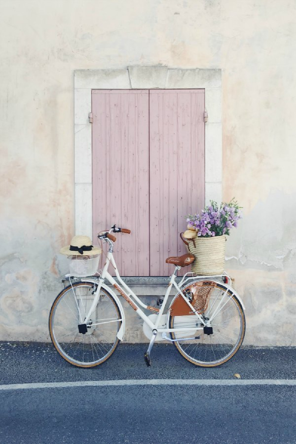 Dusty rose pink shutters on a stucco sided rustic French home with charming bicycle and French market basket (Vivi et Margot). #vivietmargot #bicycle #pink #frenchfarmhouse #frenchbasket #marketbasket #romanticdecor