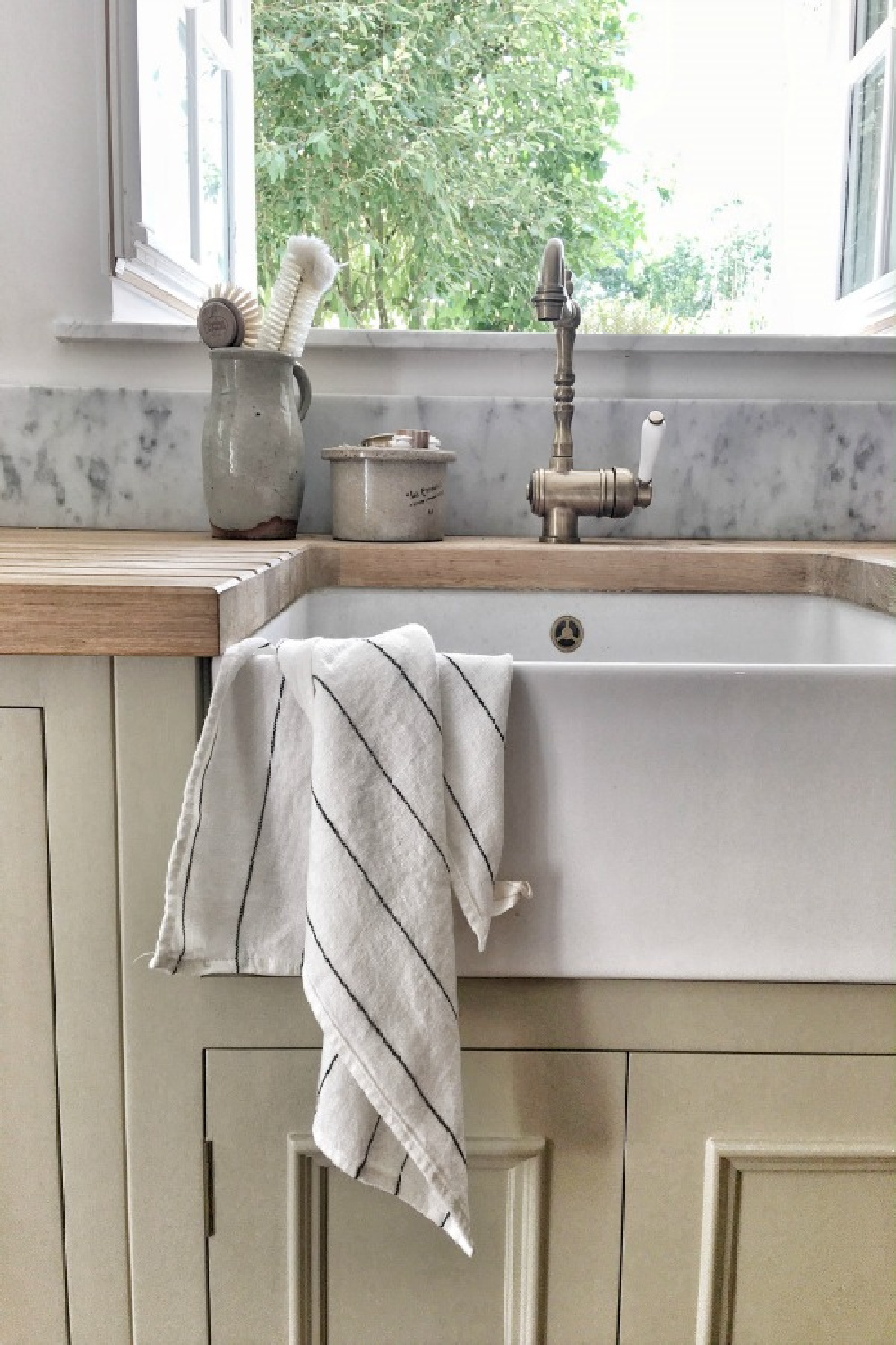 Detail of apron front fireclay farm sink in a kitchen in France. French farmhouse design inspiration, house tour, interview, and French homewares and baskets. Vivi et Margot. #frenchkitchen #farmsink #frenchfarmhouse #hellolovelystudio #frenchcountry #designinspiration #interiordesign #rusticdecor #frenchhome