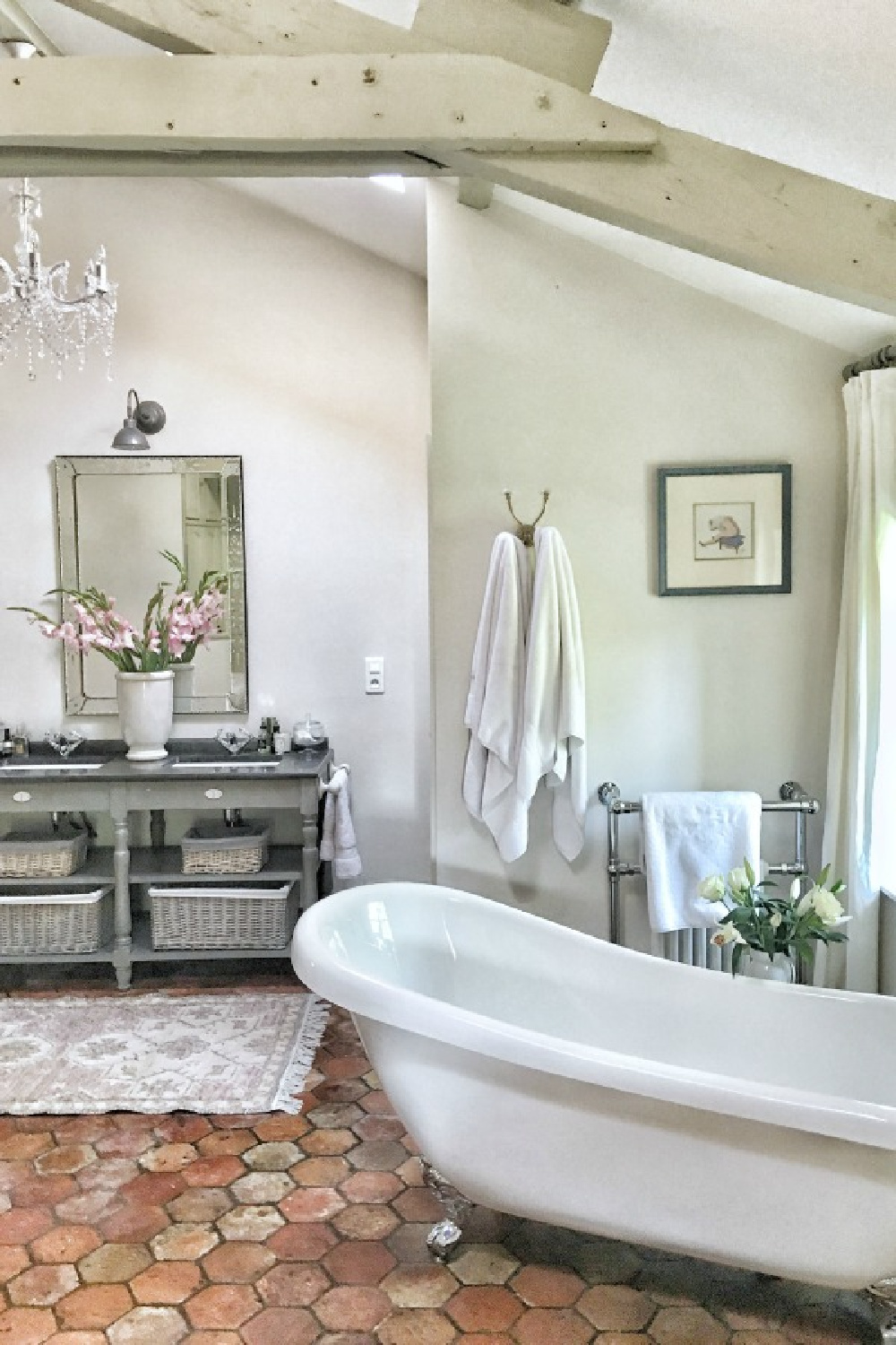 Farrow and Ball Strong White on walls in a French farmhouse bathroom.French farmhouse design inspiration with an interview with Vivi et Margot. Come be inspired on Hello Lovely and learn the paint colors used in these beautiful authentic French country interiors. #frenchbathroom #rusticdecor #frenchfarmhouse #hellolovelystudio #frenchcountry #designinspiration #interiordesign #vivietmargot #rusticdecor #frenchhome #summerliving #europeancountry