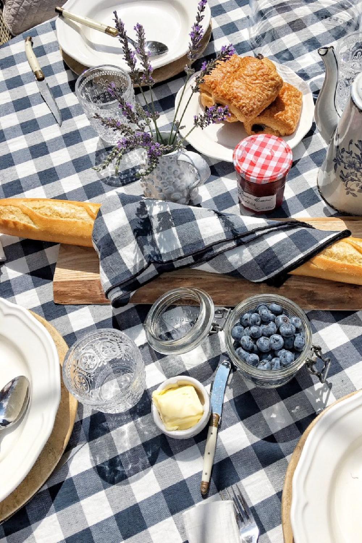 French tablescape with navy blue check linens (Maison de Vacances) from Vivi et Margot, bagutte, pastries, and berries. #vivietmargot #tablescape #check #gingham #tablecloth #baguette #dining #frenchfarmhouse