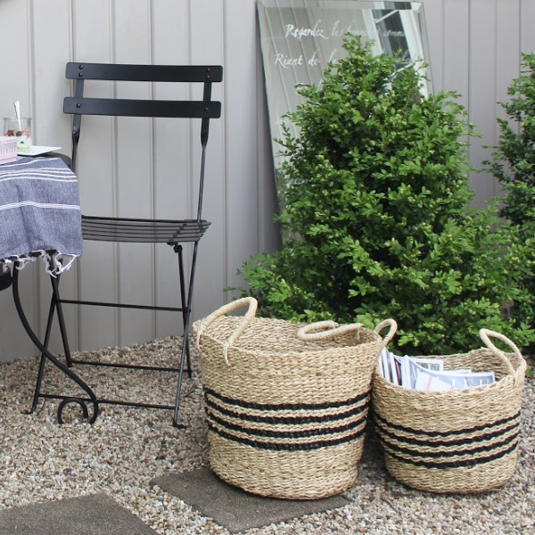 Seagrass Rrench baskets with stripes, Turkish towel runner, and outdoor oasis dining with French country romance and a table set for brunch. #hellolovelystudio #frenchbistro  #frenchbaskets #frenchcountrydecor #modernfrench #bistrochairs #outdoordining #seagrassbasket #turkishtowel