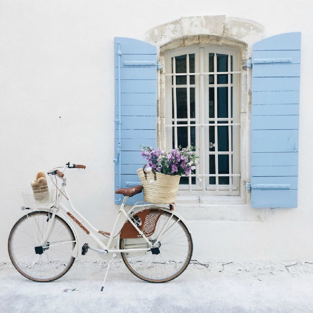 Charming French country vignette with white bicycle, French market basket of flowers, bright blue shutters, and a crisp white house exterior. Romantic indeed! Come be inspired by more French farmhouse design inspiration from Vivi et Margot on Hello Lovely. #vivietmargot #frenchfarmhouse #bicycle #frenchbasket #shutters #marketbasket #romanticdecor #frenchcountry