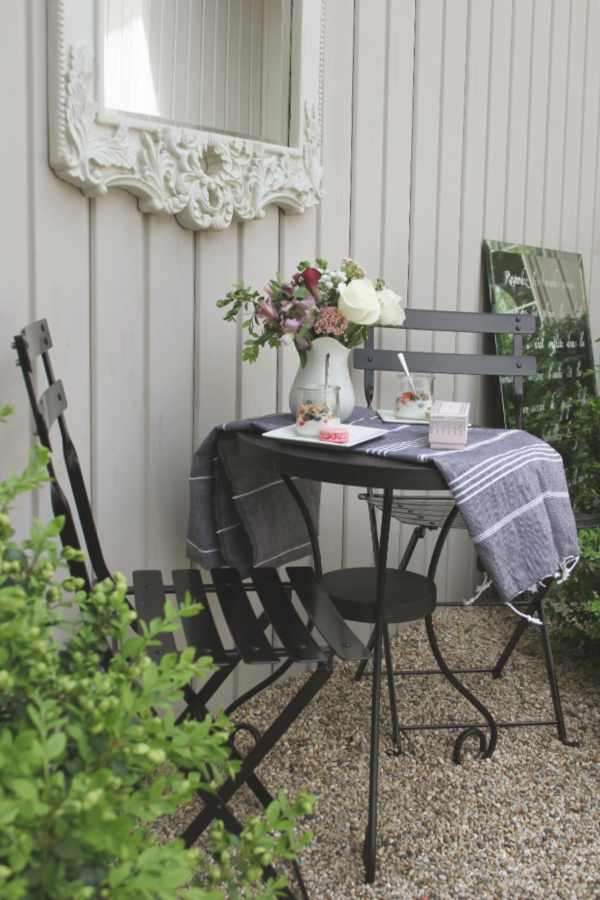 Black bistro set, Turkish towel runner, and outdoor oasis dining with French country romance and a table set for brunch. #hellolovelystudio #frenchbistro #modernfrench #bistrochair #outdoordining #turkishtowel
