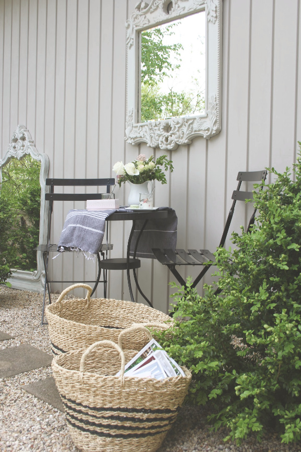 French country courtyard with boxwood, gravel, black bistro set, baskets, and a French mirror. #hellolovelystudio #cafechairs #frenchcountry #bistrochairs #outdoordining #frenchbaskets #patiofurniture #outdooroasis