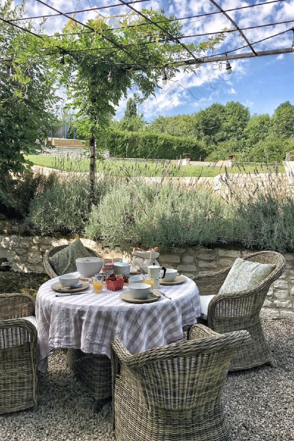 Outdoor dining in a French courtyard. Blush tablecloth by Vivi et Margot. #vivietmargot #frenchfarmhouse #outdoor #dining #kubuchair