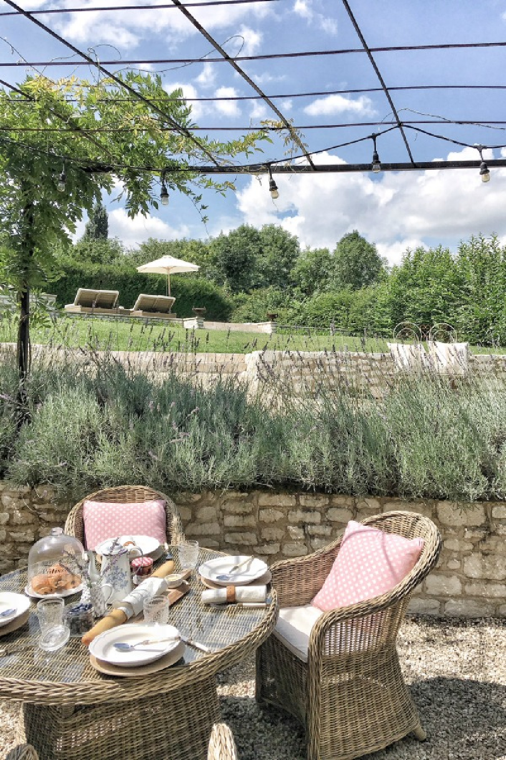 Charming outdoor dining area with kubu chairs and round table - French farmhouse by Vivi et Margot. #vivietmargot #frenchfarmhouse #dining #outdoor