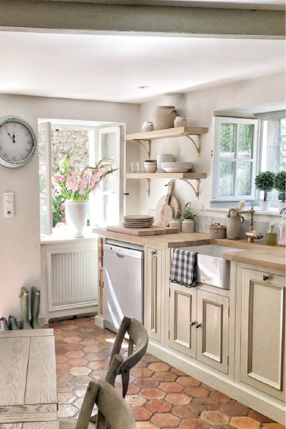 Kitchen in France with antique reclaimed hex tiles, putty cabinets, and farm sink. #frenchkitchen #frenchfarmhouse #countryfrench #kitchens #oldworldstyle #terracottatile #puttycabinets