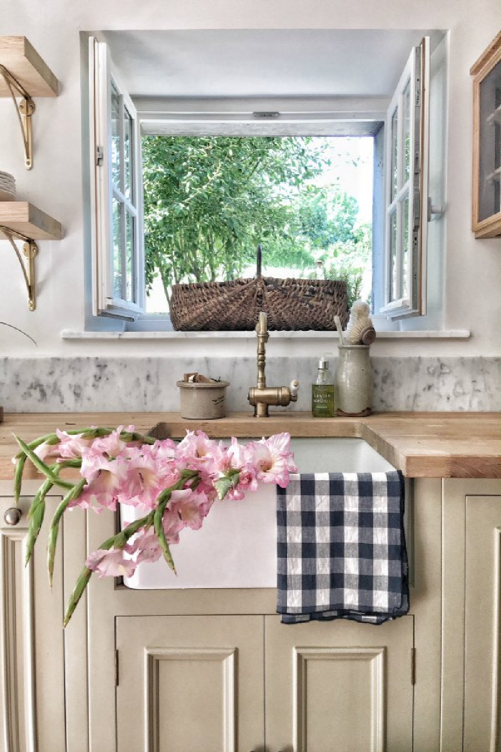 Charming French farmhouse kitchen with farm sink, checkered linens, and French baskets. A wood countertop tops putty colored cabinets. #vivietmargot #frenchkitchen #farmhousekitchen #farmsink #rusticdecor