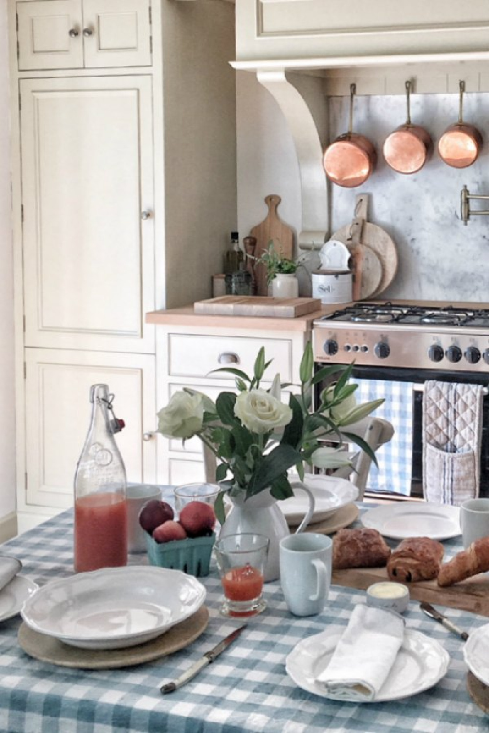 This charming kitchen near Bordeaux is rustic and romantic thanks to French homewares from Vivi et Margot. #frenchkitchen #frenchfarmhouse #gingham #tablecloth #puttycabinets #kitchendesign #rusticdecor