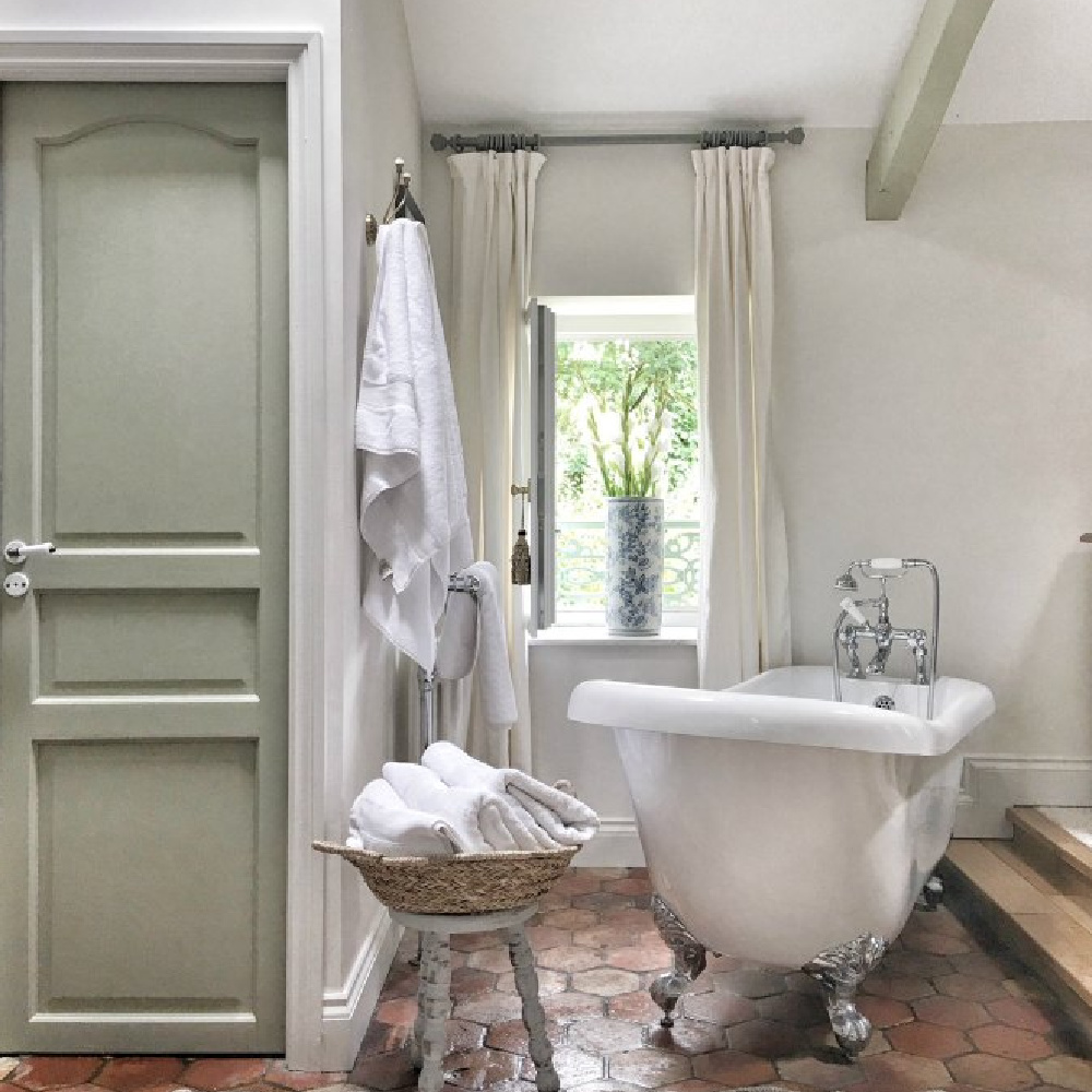Vivi et Margot's master bathroom in France has a lovely, serene mood and authentic design features. #frenchfarmhouse #bathroomdesign #oldworldstyle #rusticdecor #frenchhome