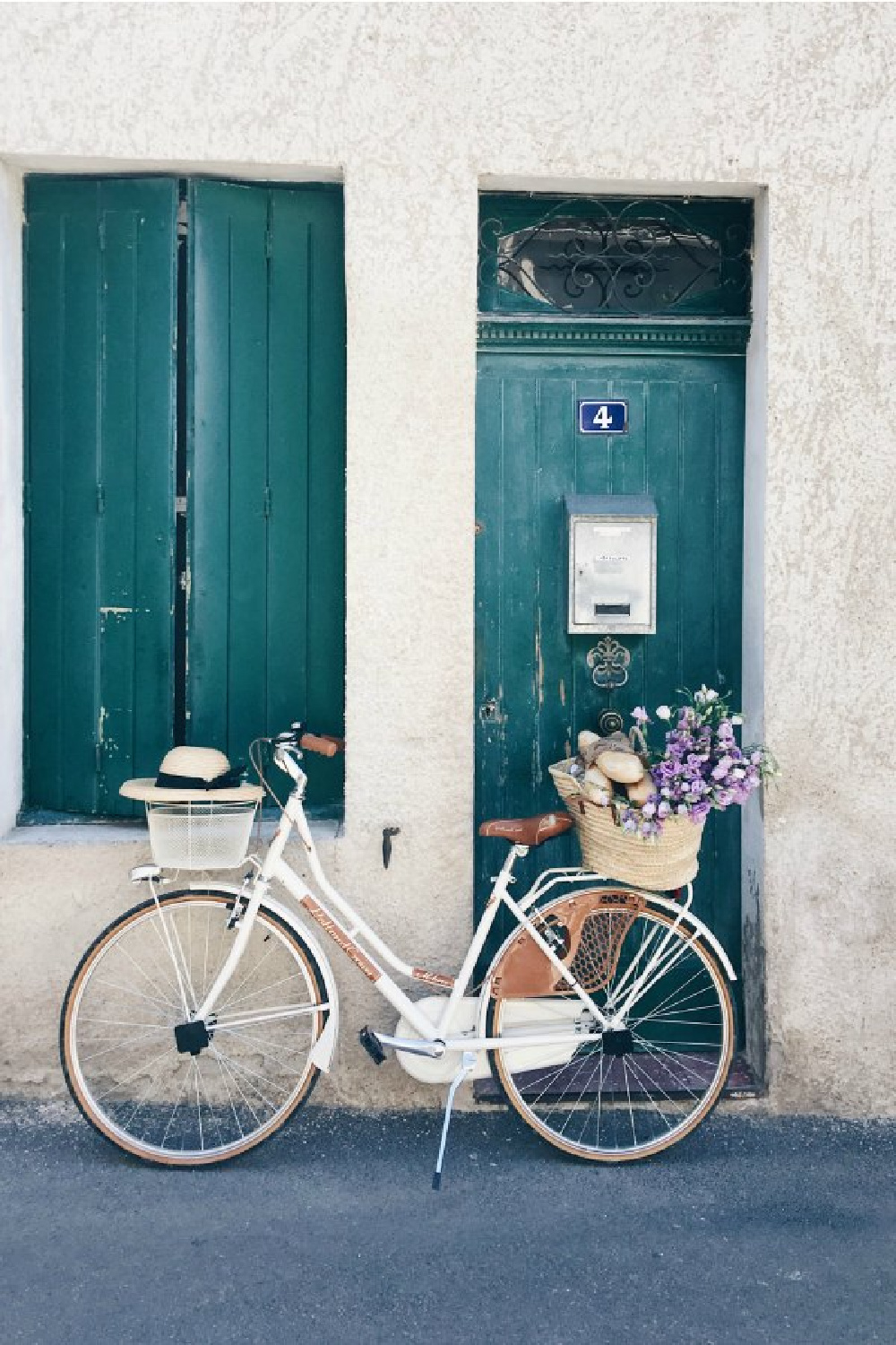 French market basket rests on a white bicycle outside of a rustic home with green shutters. Come discover beautiful French Farmhouse Design Inspiration from Vivi et Margot. #frenchfarmhouse #bicycle #marketbasket