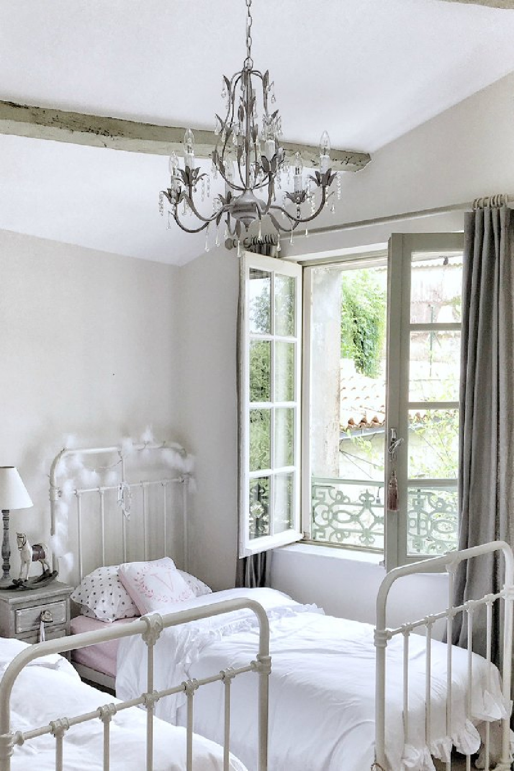 Girls bedroom in French countryside with chandelier and metal vintage beds. You'll love this photo gallery and house tour of a home near Bordeaux, France. #vivietmargot #frenchfarmhouse #rusticdecor #countryfrench #interiordesign #bedroomdecor