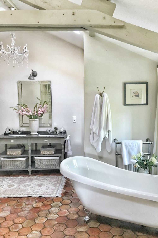 Romantic bathroom in France with clawfoot tub, terracotta tile floor, and rustic beams. #vivietmargot #frenchfarmhouse #bathroomdesign #interiordesign #oldworldstyle #clawfoottub