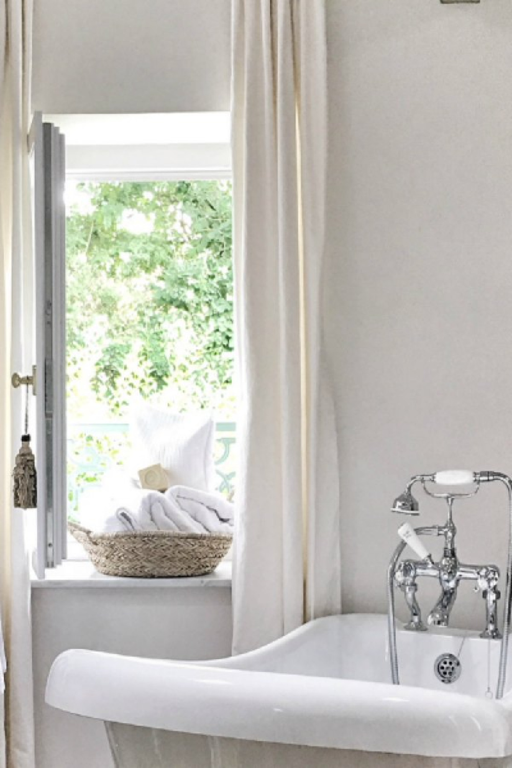 Detail of clawfoot tub near open window in a farmhouse in France.. You'll love this photo gallery and house tour of a rustically elegant farmhouse near Bordeaux by Vivi et Margot. #bathroomdesign #clawfoottub #frenchcountry