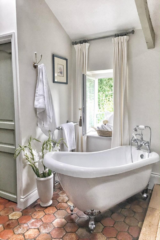 Farrow & Ball Strong White walls in a charming French bathroom with clawfoot tub. #farrowandball #strongwhite #frenchfarmhouse #bathroom #paintcolors #clawfoottub