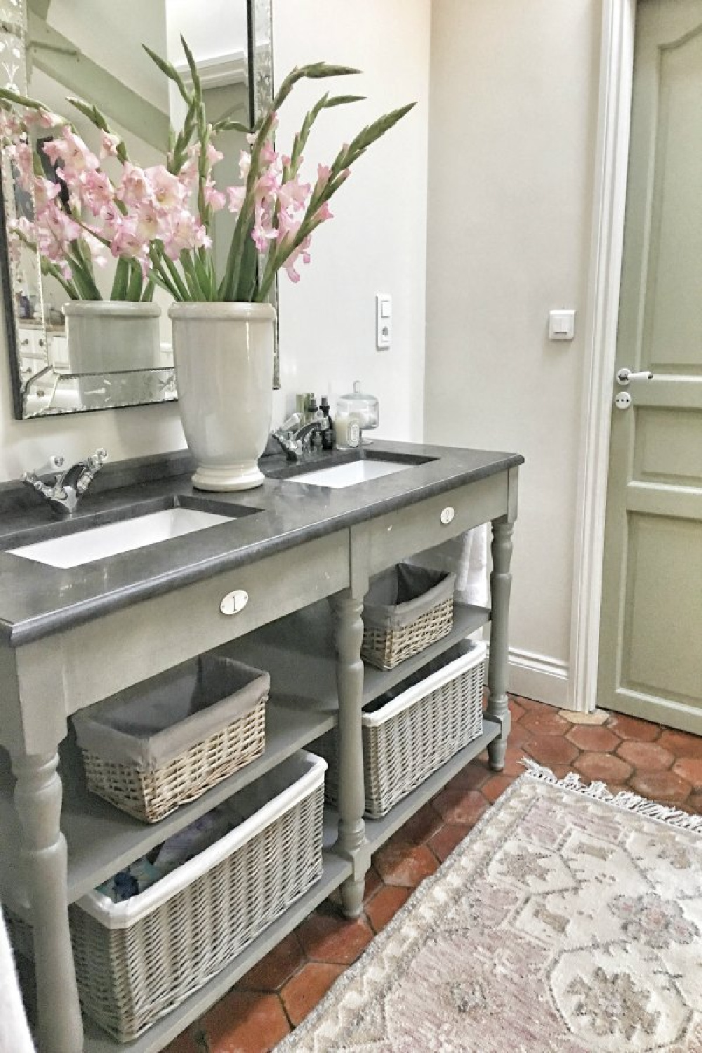 Double vanity with open shelving in romantic bath. Beautiful French farmhouse design inspiration and house tour (Vivi et Margot). #bathroomdecor #interiordesign #frenchfarmhouse #bathroomvanity