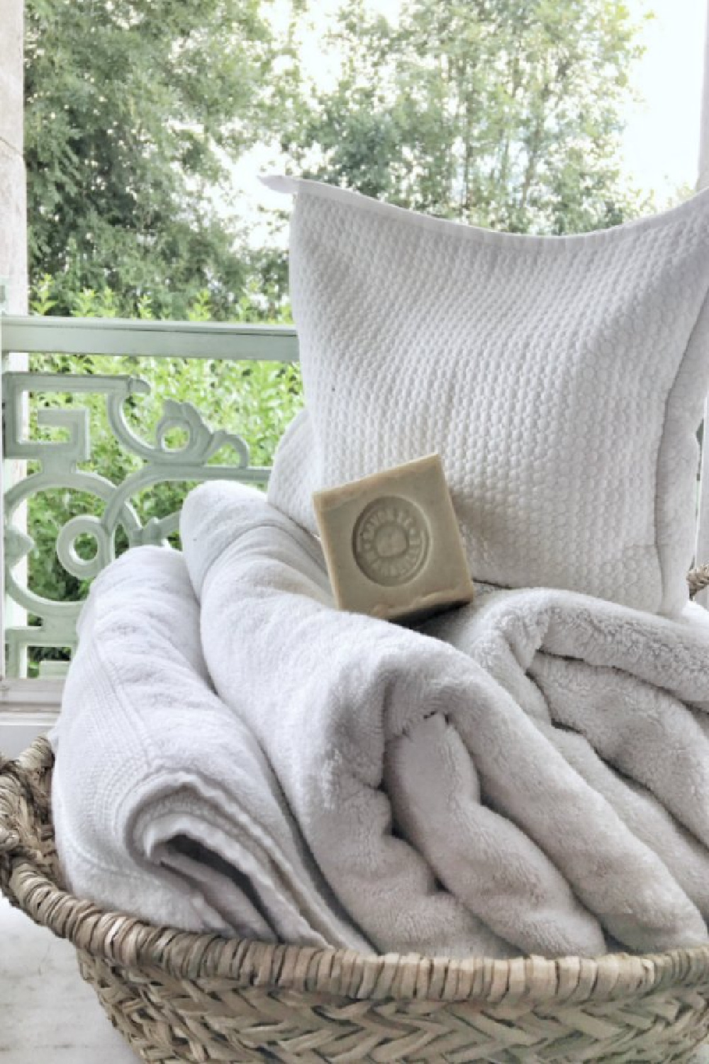 French market basket of towels and soap in a romantic French farmhouse bathroom by Vivi et Margot. #frenchfarmhouse #bathroomdecor