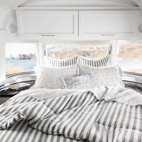 Stripe bedding and pillows. Airstream at Pottery Barn is a lovely collection of whimsical and happy camper decor whether we have a vintage camper to put in or not! #airstream #potterybarn #happycamper #whimsicalgifts #vintagecamper #homedecor #bedding