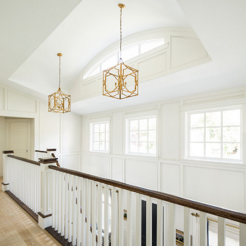 Architecturally magnificent upper stair landing with wood flooring, classic paneling, brass pendants, and an abundance of natural light. Design by The Fox Group. Come see more Timeless Interior Design Ideas. #staircase #classicarchitecture #thefoxgroup