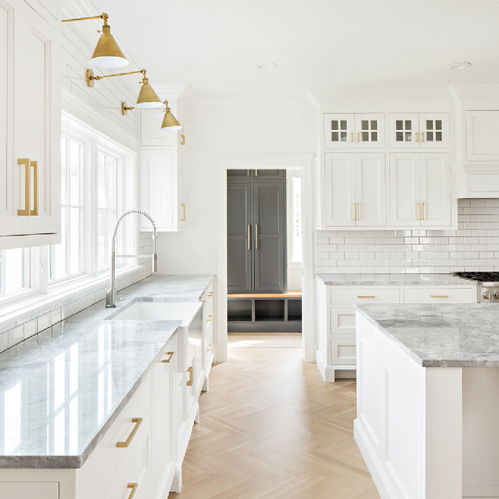 Magnificent timeless design in a white kitchen by The Fox Group. Brass library lights, white oak flooring in herringbone pattern, and quartzite countertops. Come be inspired by more Timeless Interior Design Ideas. #thefoxgroup #kitchendesign #modernfarmhouse #herringbone #classicdesign #timeless