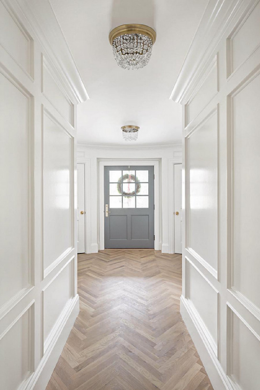 Benjamin Moore Simply White paint color on paneling in a hall. Design by The Fox Group. Herringbone wood floor and beautiful grey painted door. Come BE INSPIRED BY MORE Timeless Interior Design Ideas, Paint Colors & Furniture Finds. #thefoxgroup #benjaminmooresimlywhite #herringbone #woodfloor #interiordesigninspiration