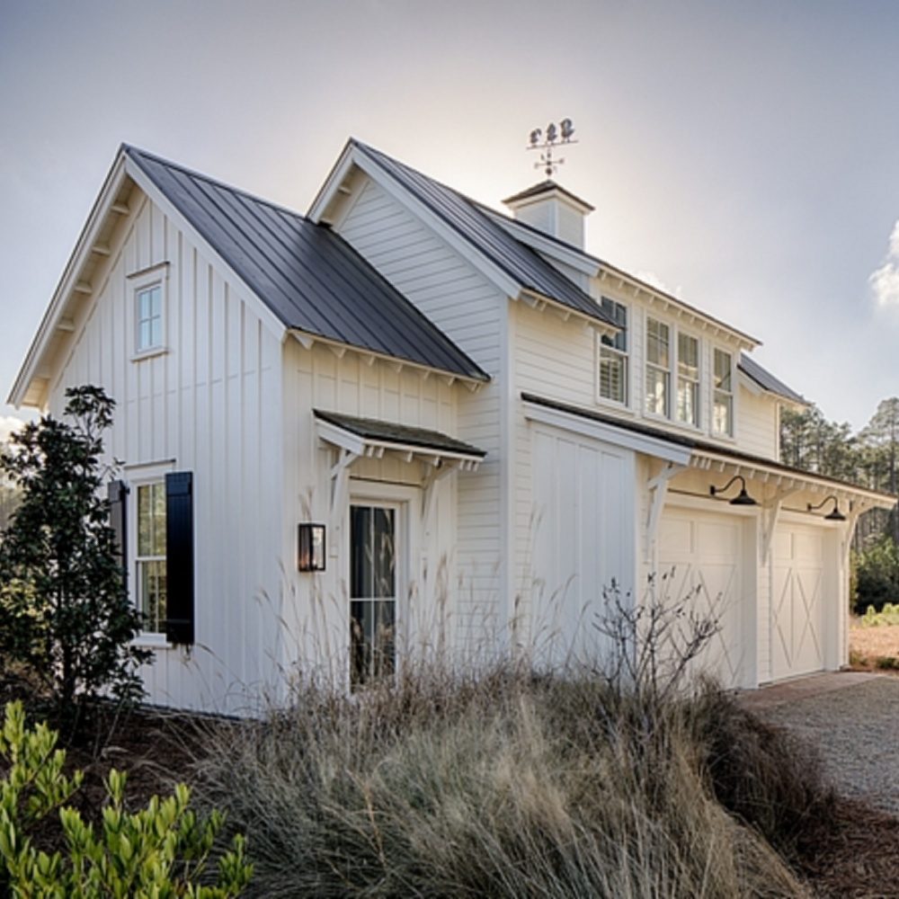 Board and batten coastal cottage exterior of a home in Palmetto Bluffs with interiors by Lisa Furey. #coastalcottage #boardandbatten #houseexteriors #whitecottage