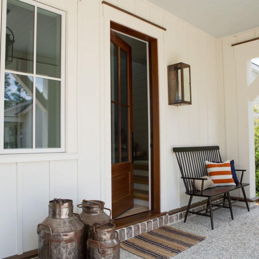 Modern farmhouse front porch of a South Carolina coastal cottage with bench and milk cans. #frontporch #cottagestyle #coastalcottage