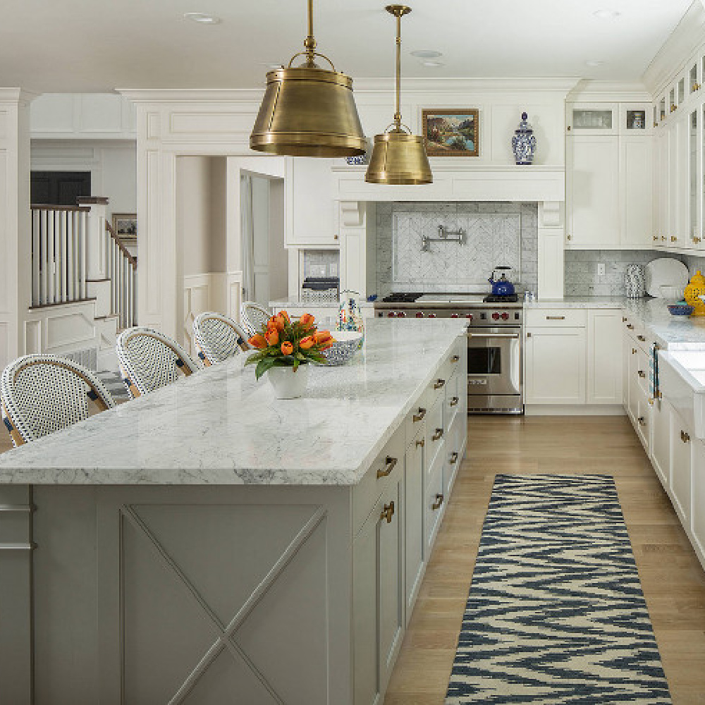 Classic kitchen by The Fox Group with brass pendant drum pendants over island and blue accents. Farm sink, white cabinetry, and Parisian counter stools. #kitchendesign #thefoxgroup #classicdesign #coastalkitchen #brasspendants