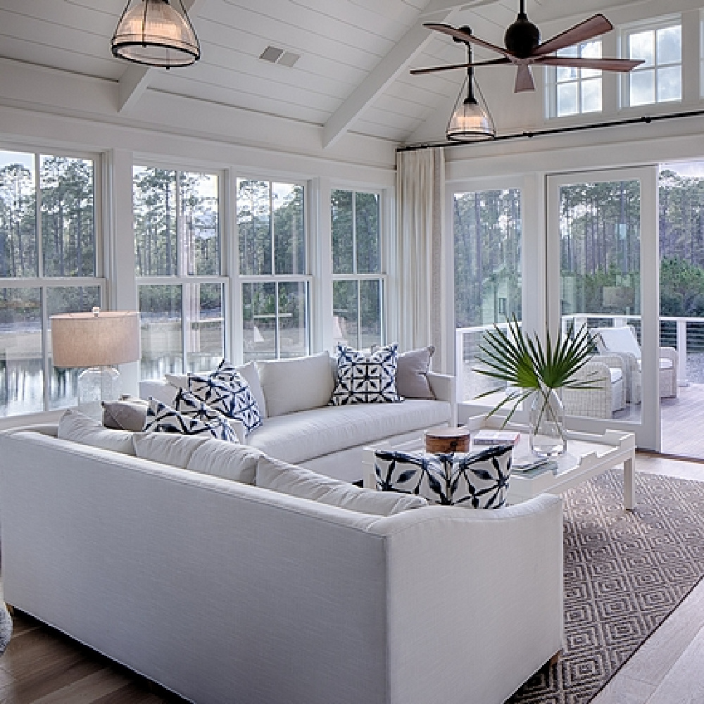 Great room with white oak flooring, white sofas, blue accessories, and shiplap in a board and batten coastal cottage in Palmetto Bluff. Modern farmhouse interior design by Lisa Furey. #greatroom #coastalstyle #blueandwhite #whiteoak #shiplap #breezystyle #interiordesign