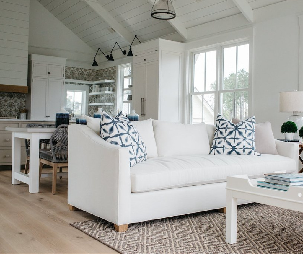 White great room, dining area, and kitchen in a board and batten coastal cottage in Palmetto Bluff. Modern farmhouse interior design with blue, white, and natural materials by Lisa Furey. #greatroom #coastalstyle #blueandwhite #interiordesign