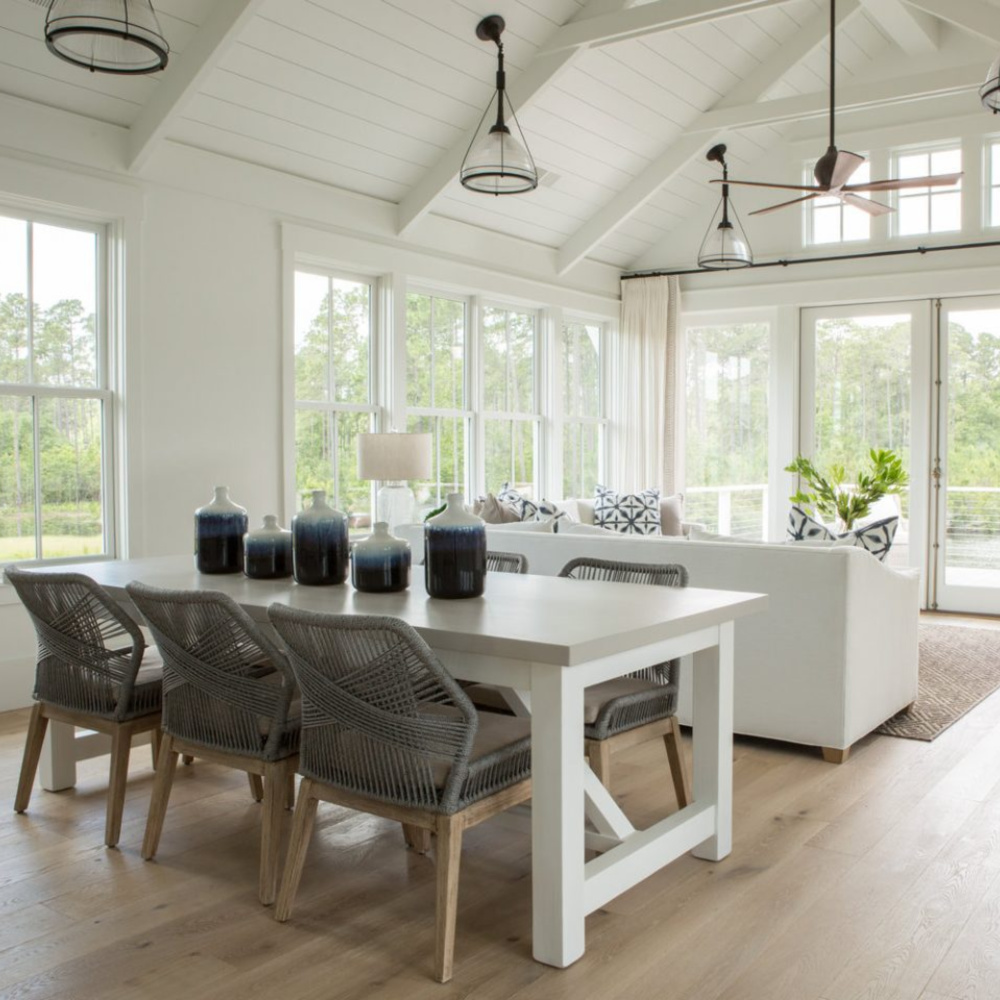 Great room and dining area iwith white oak flooring and shiplap n a board and batten coastal cottage in Palmetto Bluff. Modern farmhouse interior design by Lisa Furey. #coastalstyle #modernfarmhouse #interiordesign #greatroom #whiteoakflooring #shiplap #waterfronthome #coastalcottage