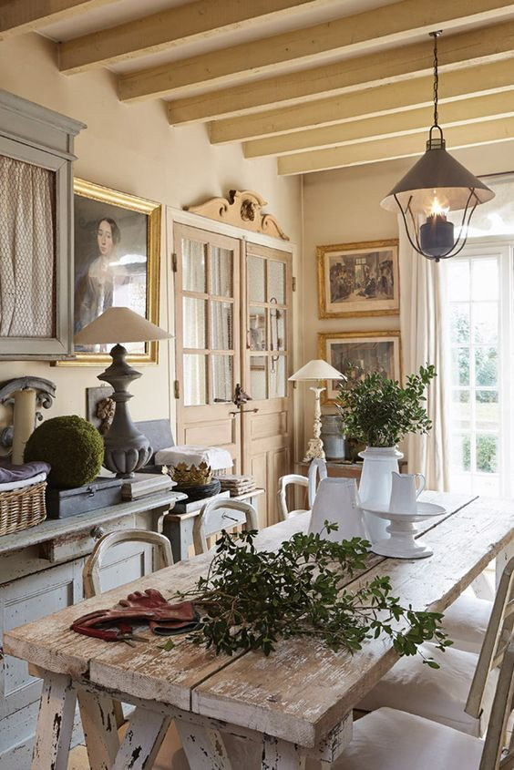 Charming French country kitchen with rustic elegant harvest table, architectural elements, and Old World style.